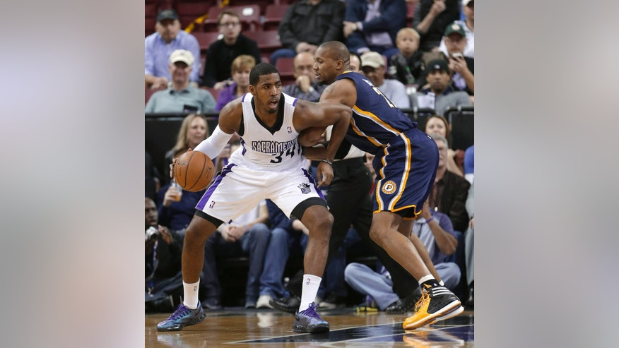 Sacramento Kings forward Jason Thompson, left, drives against Indiana Pacers forward David West during the first quarter of an NBA basketball game in Sacramento, Calif., Friday, Jan. 24, 2014. (AP Photo/Rich Pedroncelli)