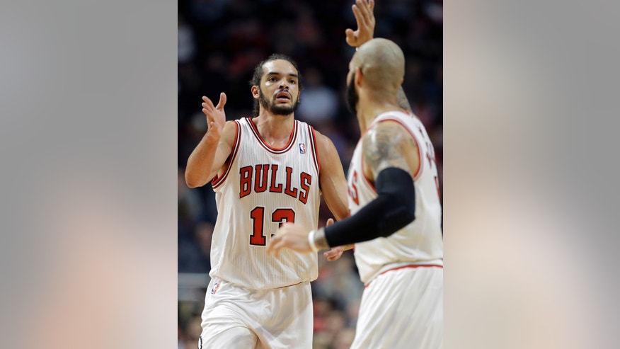 Chicago Bulls center Joakim Noah, left, celebrates with forward Carlos Boozer after scoring a basket during the first half of an NBA basketball game against the Los Angeles Clippers in Chicago on Friday, Jan. 24, 2014. (AP Photo/Nam Y. Huh)