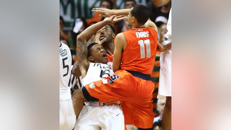 Miami's Rion Brown (5) reacts after he failed to block Syracuse's Tyler Ennis (11) from passing the ball during the second half of a NCAA college basketball game in Coral Gables, Fla., Saturday, Jan. 25, 2014. Syracuse won 64-52. (AP Photo/J Pat Carter)