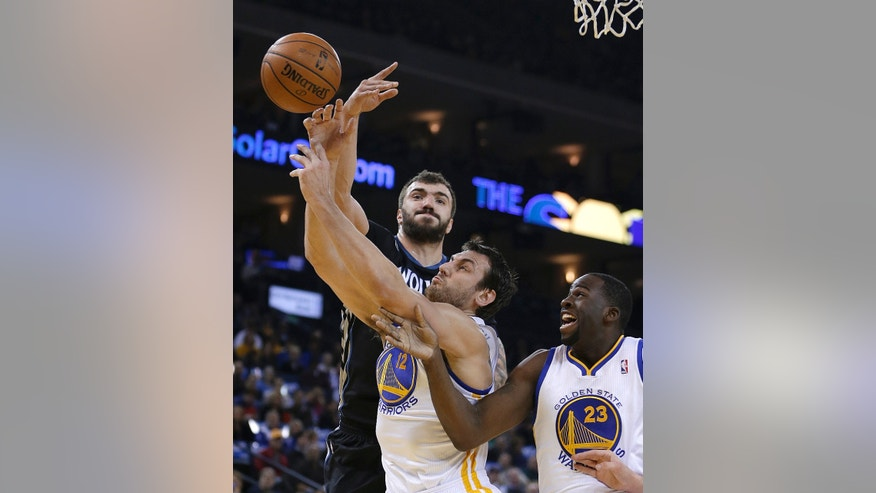 Minnesota Timberwolves' Nikola Pekovic, left, and Golden State Warriors' Andrew Bogut (12) reach for a rebound during the first half of an NBA basketball game Friday, Jan. 24, 2014, in Oakland, Calif. At right is Warriors' Draymond Green (23). (AP Photo/Ben Margot)