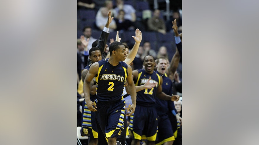 Marquette guard John Dawson (2) heads downcourt after making a 3-point shot as his teammates celebrate, during overtime of an NCAA college basketball game against Georgetown, Monday, Jan. 20, 2014, in Washington. Marquette won 80-72 in overtime. (AP Photo/Alex Brandon)