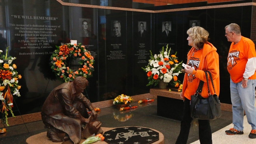 Oklahoma State University alumni Mary McCroskey, left, and Freddy McCroskey, right, of Oklahoma City, view the memorial to the the 10 men killed in the Jan. 27, 2001 Oklahoma State plane crash before the start of an NCAA college basketball game between West Virginia and Oklahoma State in Stillwater, Okla., Saturday, Jan. 25, 2014. (AP Photo/Sue Ogrocki)