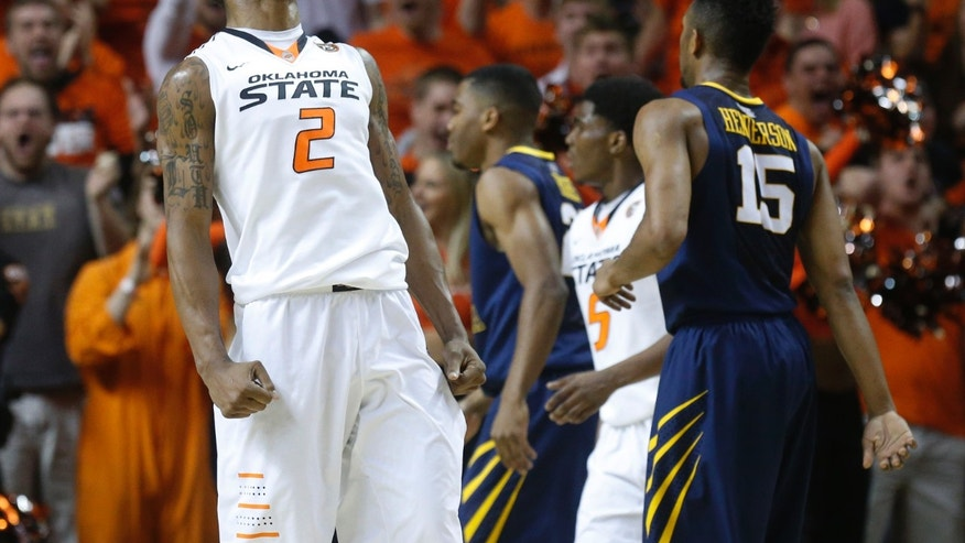 Oklahoma State wing Le'Bryan Nash (2) reacts after dunking near the close of the first half of an NCAA college basketball game against West Virginia in Stillwater, Okla., Saturday, Jan. 25, 2014. West Virginia guard Terry Henderson (15) is at right. (AP Photo/Sue Ogrocki)