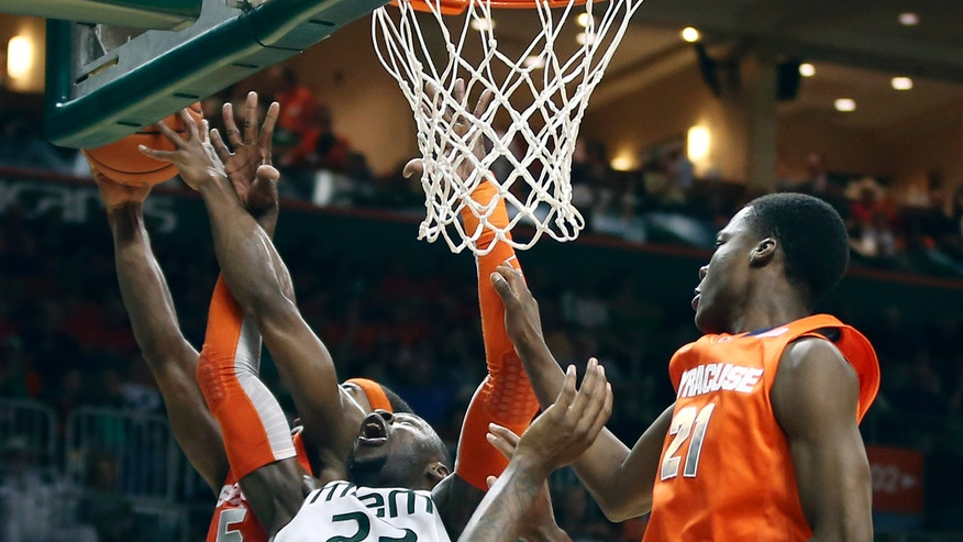 Miami's Tonye Jekiri (2) battle for the ball Syracuse's C.J. Fair (5) and Tyler Roberson (21) during the first half of an NCAA college basketball game in Coral Gables, Fla., Saturday, Jan. 25, 2014. (AP Photo/J Pat Carter)