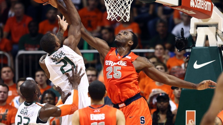 Syracuse's Rakeem Christmas (25) blocks Miami's Erik Swoope (21) during the first half of an NCAA college basketball game in Coral Gables, Fla., Saturday, Jan. 25, 2014. (AP Photo/J Pat Carter)