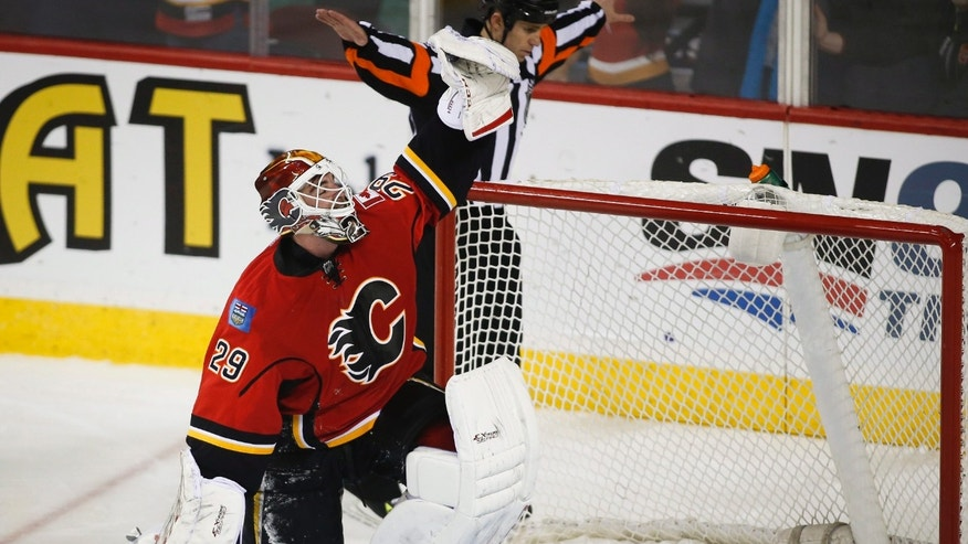 Calgary Flames goalie Reto Berra, from Switzerland, celebrates the teams win overtime shootout NHL hockey action against the Nashville Predators in Calgary, Alberta, Friday, Jan. 24, 2014. The Calgary Flames beat the Nashville Predators 5-4 in a shootout. (AP Photo/The Canadian Press, Jeff McIntosh)