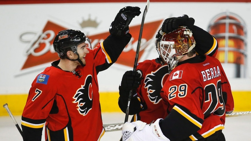 Calgary Flames goalie Reto Berra, right, from Switzerland, celebrates the team's win with teammate TJ Brodie following overtime shootout NHL hockey action against the Nashville Predators in Calgary, Alberta, Friday, Jan. 24, 2014. The Calgary Flames beat the Nashville Predators 5-4 in a shootout. (AP Photo/The Canadian Press, Jeff McIntosh)