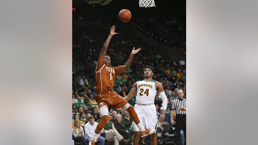 Texas guard Isaiah Taylor, left, scores past Baylor's Ish Wainright (24) during the second half of an NCAA college basketball game, Saturday, Jan. 25, 2014, in Waco, Texas. Texas won 74-60.  AP Photo/Waco Tribune Herald, Michael Bancale)