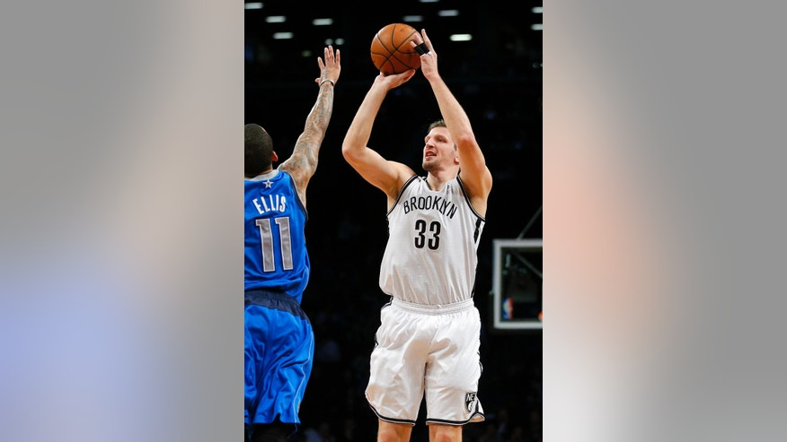Brooklyn Nets power forward Mirza Teletovic (33) shoots a three point shot over Dallas Mavericks shooting guard Monta Ellis (11) in the second quarter of an NBA basketball game on Friday, Jan. 24, 2014, in New York. (AP Photo/Paul J. Bereswill)