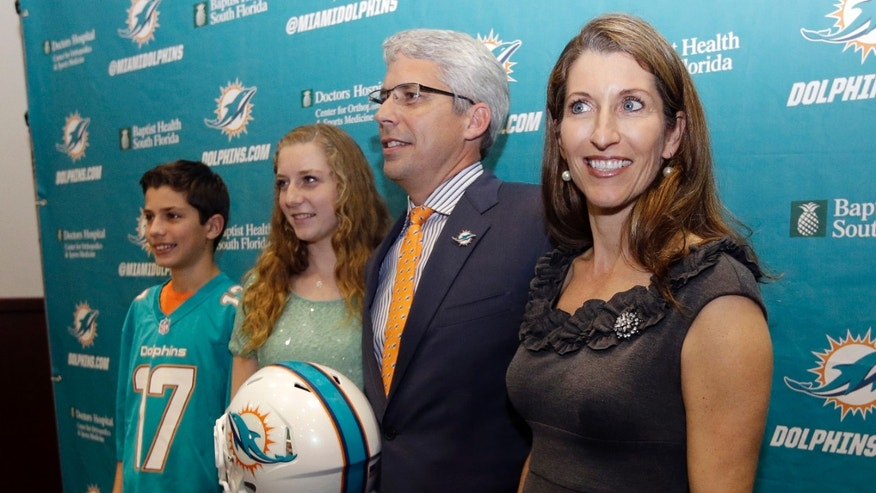 Dennis Hickey, new general manager for the Miami Dolphins football team, second from right, poses with his wife Stephanie, right, son Barrett, left, and daughter Breanna, second from left, after being introduced during a news conference, Tuesday, Jan. 28, 2014, in Davie, Fla. (AP Photo/Lynne Sladky)