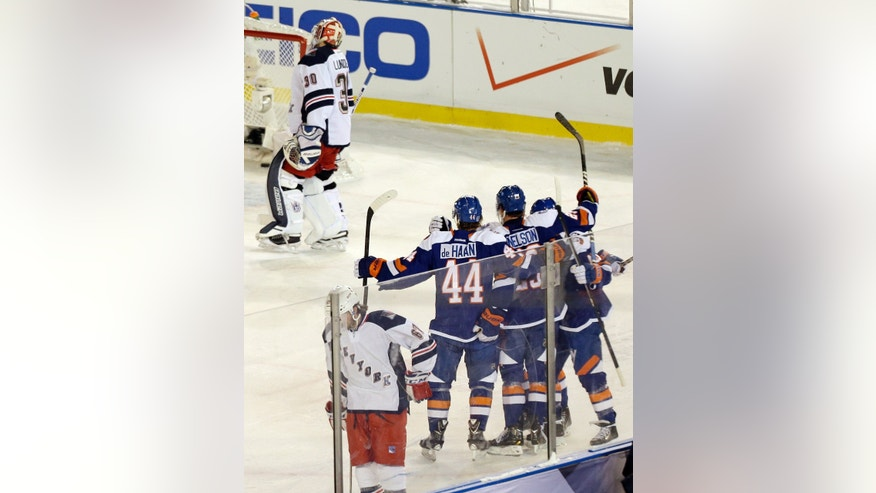 New York Rangers goalie Henrik Lundqvist (30) and teammate Benoit Pouliot (67) react as the New York Islanders celebrate a goal by Brock Nelson during the second period of an outdoor NHL hockey game  Wednesday, Jan. 29, 2014, at Yankee Stadium in New York. (AP Photo/Frank Franklin II)