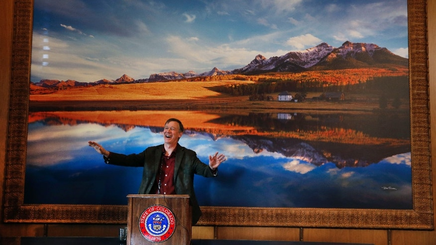 "In this Dec. 19, 2013 file photo, Colo. Gov. John Hickenlooper laughs while speaking  during a news conference in his office at the Capitol, in Denver. Behind him is a picture of the Sneffels Range of Colorado's San Juan Mountains. In the run up to the Super Bowl between the Broncos and the Seahawks, Colorado Gov. John Hickenlooper announced Wednesday, Jan. 29, 2014  that he's temporarily re-naming Colorado's highest mountains for each member of the Denver Broncos. The state is home to more than 50 mountains over 14,000 feet, called ""14-ers"" by locals. (AP Photo/Brennan Linsley, File)"