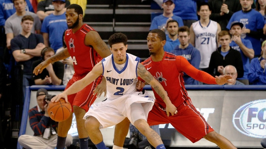 Saint Louis' Austin McBroom (2) controls the ball in front of Richmond's Derrick Williams (34), left, and  Cedrick Lindsay (2), right, during the first half of an NCAA college basketball game Wednesday, Jan. 29, 2014, in St. Louis. (AP Photo/Scott Kane)