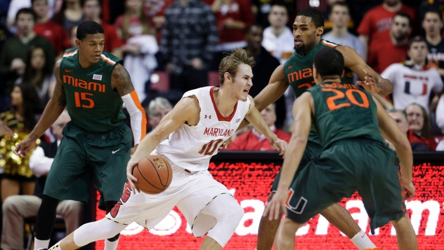 Maryland guard Jake Layman, center, drives past Miami guard Rion Brown, from left, forward Donnavan Kirk and guard Manu Lecomte in the first half of an NCAA college basketball game in College Park, Md., Wednesday, Jan. 29, 2014. (AP Photo/Patrick Semansky)