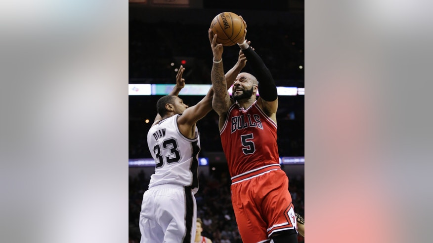 Chicago Bulls' Carlos Boozer (5) shoots as San Antonio Spurs' Boris Diaw (33) defends during the second half of an NBA basketball game, Wednesday, Jan. 29, 2014, in San Antonio. (AP Photo/Eric Gay)