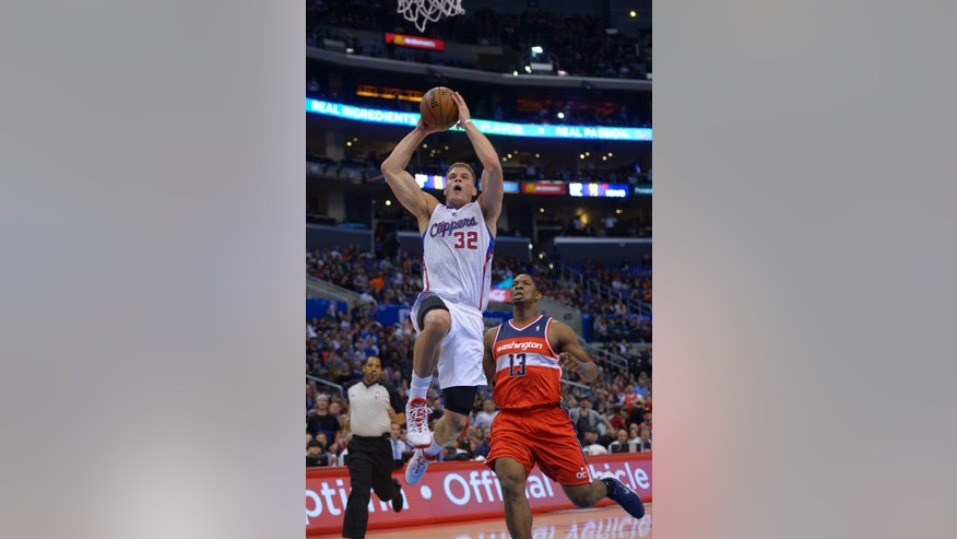 Los Angeles Clippers forward Blake Griffin, left, goes up for a dunk as Washington Wizards center Kevin Seraphin, of France, defends during the first half of an NBA basketball game, Wednesday, Jan. 29, 2014, in Los Angeles. (AP Photo/Mark J. Terrill)