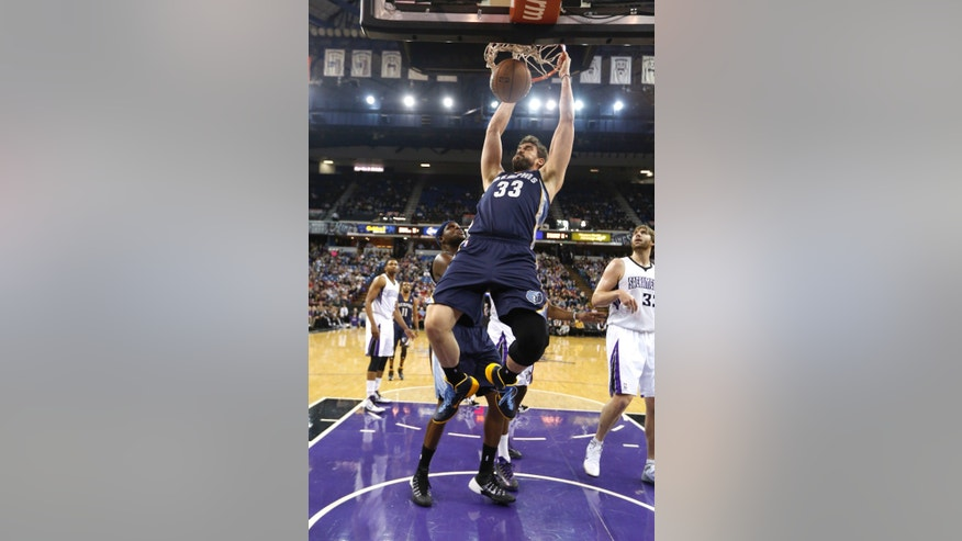 Memphis Grizzlies center Marc Gasol, of Spain, hangs on the rim after stuffing against  Sacramento Kings center Aaron Gray, right,  during the first quarter of an NBA basketball game in Sacramento, Calif., Wednesday, Jan. 29, 2014.(AP Photo/Rich Pedroncelli)
