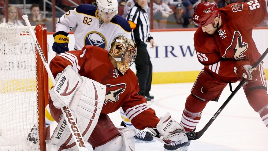 With the help of Phoenix Coyotes' Derek Morris (53), Coyotes goalie Thomas Greiss (1), of Germany, makes a save on a shot as Buffalo Sabres' Marcus Foligno (82) looks on during the first period of an NHL hockey game on Thursday, Jan. 30, 2014, in Glendale, Ariz. (AP Photo)