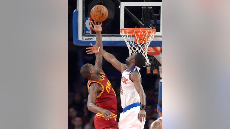 Cleveland Cavaliers' Kyrie Irving, left, puts up a shot as New York Knicks' Tim Hardaway Jr. defends during the first quarter of an NBA basketball game Thursday, Jan. 30, 2014, at Madison Square Garden in New York. (AP Photo/Bill Kostroun)
