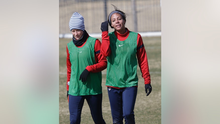 In this photo made Tuesday, Jan. 28, 2014, U.S. women's soccer team player Sydney Leroux, right, walks with teammate Megan Rapinoe after practice in Frisco, Texas. The U.S. women's soccer team opens its season against Canada in Texas on Friday, Jan. 31, their second meeting since the 2012 Olympic match. (AP Photo)