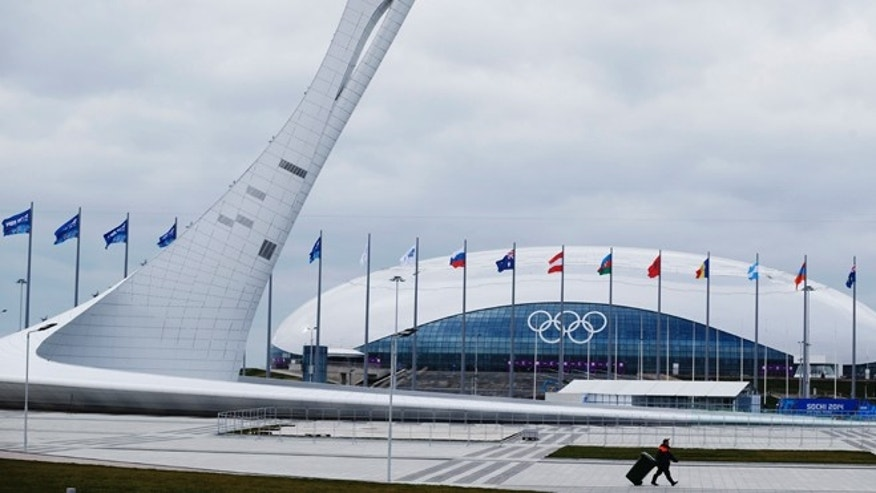 Jan. 30, 2014: A worker walks past the Olympic torch and the Bolshoy Ice Dome in the Olympic Park as construction and clean-up continues ahead of the 2014 Winter Olympics.