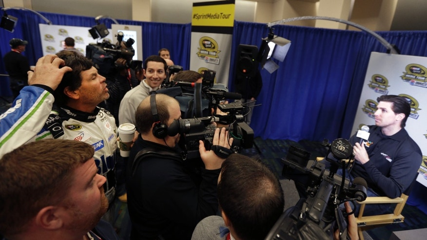 Driver/owner Michael Waltrip, left, jokes with driver Denny Hamlin, right, about his hair during a news conference at the NASCAR Sprint Cup auto racing Media Tour in Charlotte, N.C., Thursday, Jan. 30, 2014. (AP Photo)
