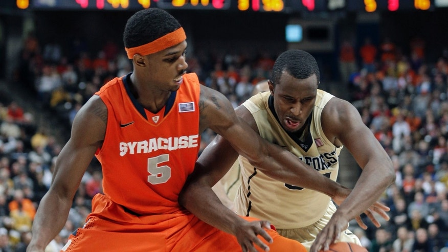 Syracuse's C.J. Fair, left, and Wake Forest's Travis McKie, right, chase a loose ball during the second half of an NCAA college basketball game in Winston-Salem, N.C., Wednesday, Jan. 29, 2014. Syracuse won 67-57. (AP Photo/Chuck Burton)