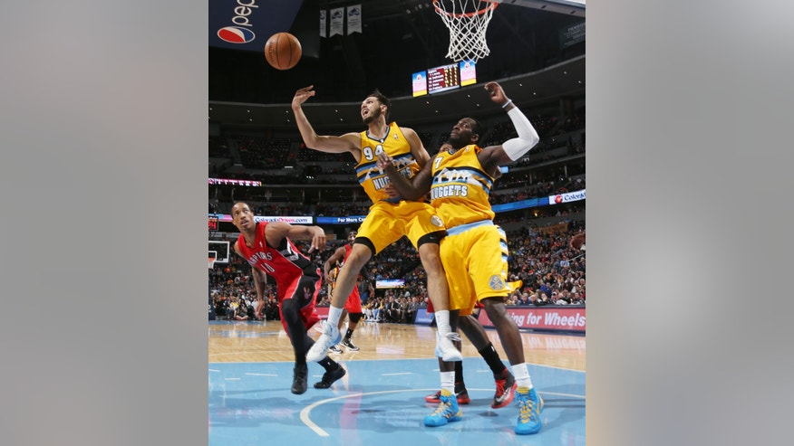 Denver Nuggets guard Evan Fournier, center, of France, reaches out for loose ball as forward J.J. Hickson, right, and Toronto Raptors guard DeMar DeRozan, left, cover in the third quarter of an NBA basketball game in Denver, Friday, Jan. 31, 2014. (AP Photo/David Zalubowski)