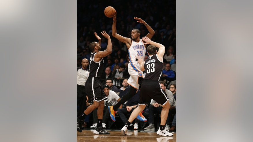 Oklahoma City Thunder's Kevin Durant, center, passes between Brooklyn Nets' Mirza Teletovic, right, and Alan Anderson during the first half of an NBA basketball game Friday, Jan. 31, 2014, in New York. (AP Photo/Seth Wenig)