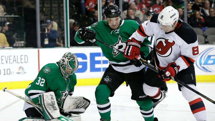 Dallas Stars' Kari Lehtonen (32), of Finland, attempts to reach a loose puck as Stars' Sergei Gonchar (55), of Russia, fights off pressure from New Jersey Devils' Dainius Zubrus (8), of Lithuania, in the second period of an NHL hockey game on Thursday, Jan. 30, 2014, in Dallas. (AP Photo/Tony Gutierrez)