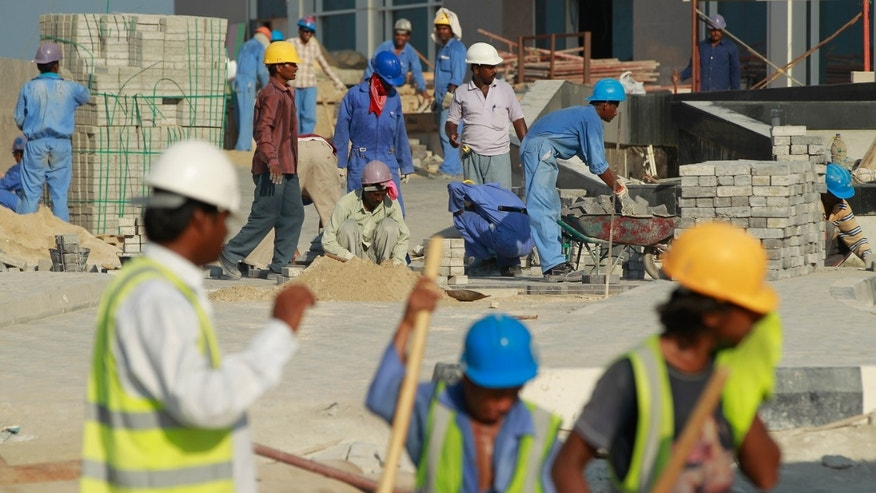 DOHA, QATAR - OCTOBER 24: Foreign workers lay an entrance road at the construction site of a new hotel in the new City Center and West Bay district on October 24, 2010 in Doha, Qatar. The International Monetary Fund (IMF) recently reiterated its projection for the Qatari economy with predictions of double digit growth for 2010 and 2011. Though natural gas and petroleum production are still the biggest two single sources of income, the non-energy sector overtook oil and gas in Qatari GDP for 2009. Qatar is heavily dependant on foreign labour from countries such as India, Sri Lanka, Bangladesh, the Phillipines and other Arab countries. Foreigners make up approximately two thirds of the Qatari population.  (Photo by Sean Gallup/Getty Images)