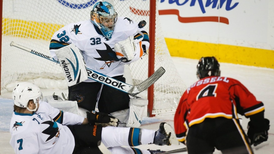 San Jose Sharks goalie Alex Stalock, center, stops a shot from Calgary Flames' Kris Russell, right, during second period NHL hockey action in Calgary, Canada, Thursday, Jan. 30, 2014. (AP Photo/The Canadian Press, Jeff McIntosh)