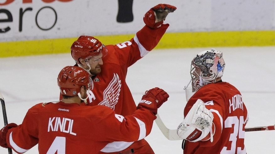 Detroit Red Wings goalie Jimmy Howard (35) is congratulated by Jakub Kindl (4), of the Czech Republic, and Niklas Kronwall (55), of Sweden, after Detroit's 4-3 win over the Washington Capitals in a shootout in an NHL hockey game in Detroit, Friday, Jan. 31, 2014. (AP Photo/Carlos Osorio)