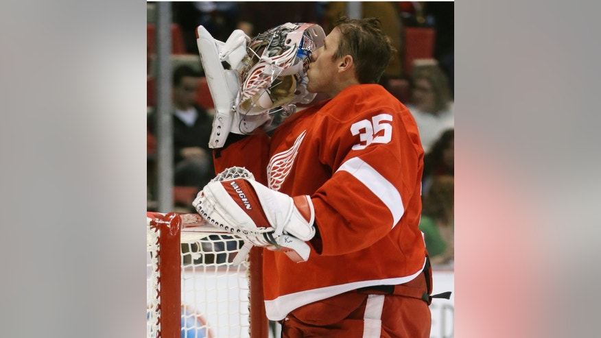 Detroit Red Wings goalie Jimmy Howard kisses his helmet during the first period of an NHL hockey game against the Washington Capitals in Detroit, Friday, Jan. 31, 2014. (AP Photo/Carlos Osorio)