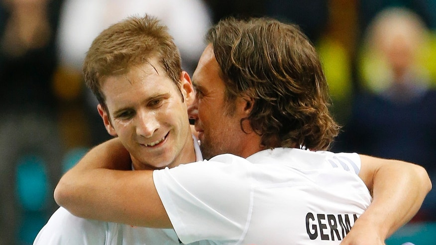 Germany's Florian Mayer, left, celebrates with team captain Carsten Arriens after beating Spain's Feliciano Lopez during a Davis Cup World Group first round tennis match between Germany and Spain in Frankfurt, Germany, Friday, Jan. 31, 2014. (AP Photo/Michael Probst)