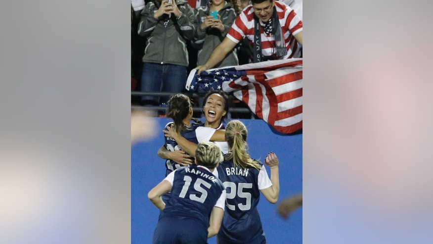 United States forward Sydney Leroux, center, celebrates after scoring her goal with teammates Christen Press (23), Morgan Brian (25) and Megan Rapinoe (15) during the second half of a soccer game against Canada, Friday, Jan. 31, 2014, in Frisco, Texas. (AP Photo/LM Otero)