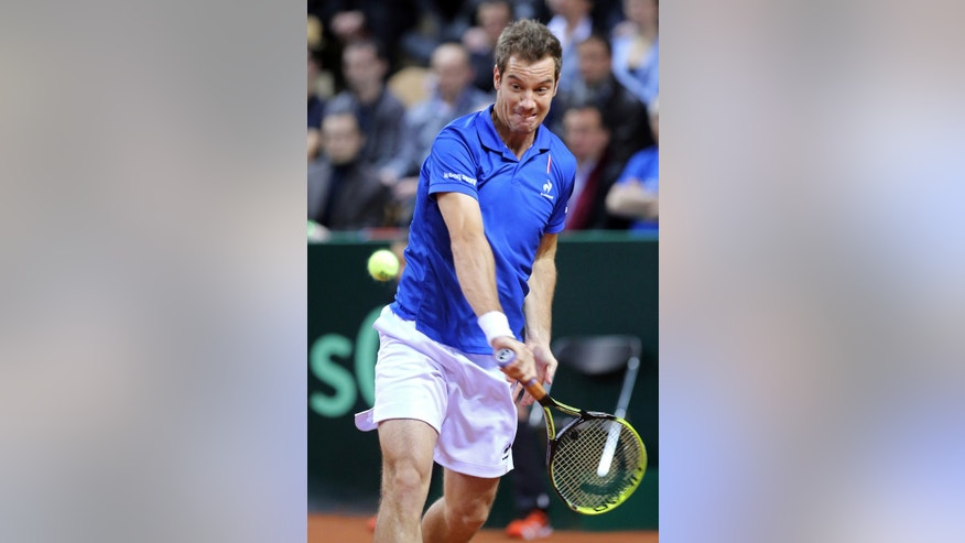 France's Richard Gasquet returns the ball to Australia's Nick Kyrgios during their singles match, in the first round of the Davis Cup between France and Australia, in La Roche sur Yon, western France, Friday Jan. 31, 2014.(AP Photo/Remy de la Mauviniere)
