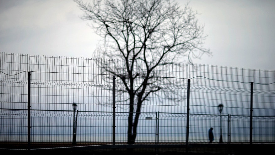 Jan. 31, 2014 - A security fence lines the perimeter of the Olympic Park as a policeman at right patrols along the boardwalk on the Black Sea ahead of the 2014 Winter Olympics in Sochi, Russia.