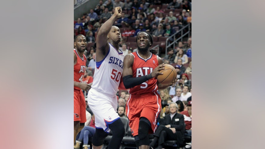 Atlanta Hawks' DeMarre Carroll (5) looks to pass as Philadelphia 76ers' Lavoy Allen (50) defends in the first half of an NBA basketball game, Friday, Jan. 31, 2014, in Philadelphia. (AP Photo/H. Rumph Jr.)