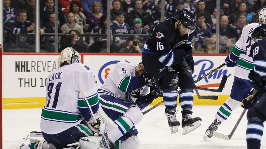 Vancouver Canucks' Jason Garrison (5) is hit by Winnipeg Jets' Andrew Ladd (16) as he jumps to avoid a shot during the second period of an NHL hockey game in Winnipeg, Manitoba, on Friday, Jan. 31, 2014. (AP Photo/The Canadian Press, John Woods)