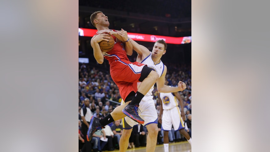Los Angeles Clippers' Blake Griffin, left,  is fouled as he goes up for a shot by Golden State Warriors' David Lee, right, during the first half of an NBA basketball game on Thursday, Jan. 30, 2014, in Oakland, Calif. (AP Photo)