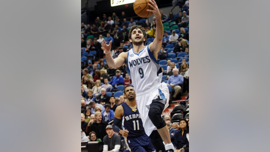Minnesota Timberwolves' Ricky Rubio, right, of Spain, lays up a basket as Memphis Grizzlies' Mike Conley watches in the first quarter of an NBA basketball game on Friday, Jan. 31, 2014, in Minneapolis. (AP Photo/Jim Mone)
