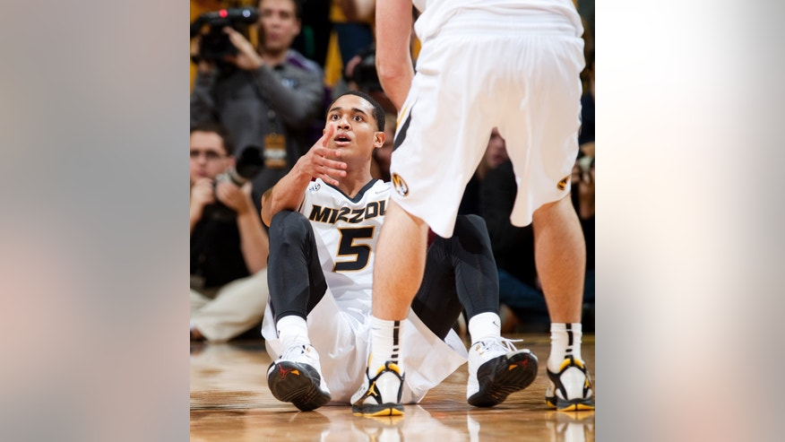 Missouri's Jordan Clarkson is helped up off the court as he looks at the referee in disbelief after he thought he was fouled during the second half of an NCAA college basketball game against Kentucky Saturday, Feb. 1, 2014, in Columbia, Mo. Kentucky won the game 84-79. (AP Photo/L.G. Patterson)