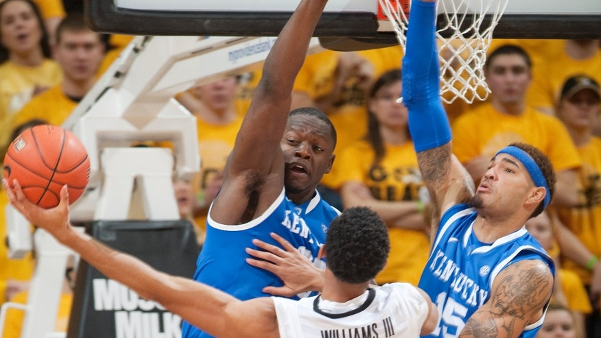Missouri's Johnathan Williams III, center, tries to shoot past Kentucky's Willie Cauley-Stein, right, and Julius Randle during the second half of an NCAA college basketball game Saturday, Feb. 1, 2014, in Columbia, Mo. Kentucky won the game 84-79. (AP Photo/L.G. Patterson)
