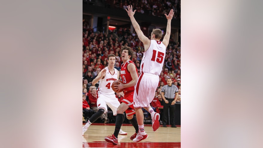 Ohio State's Amedeo Della Valle, center, shoots between Wisconsin's Frank Kaminsky, left, and Sam Dekker (15) during the first half of an NCAA college basketball game Saturday, Feb. 1, 2014, in Madison, Wis. (AP Photo/Andy Manis)