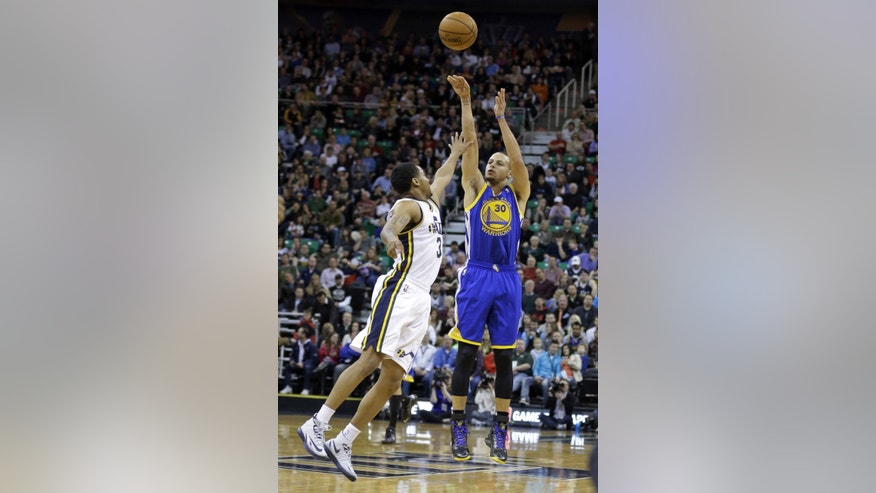 Utah Jazz's Trey Burke, left, defends against Golden State Warriors' Stephen Curry (30) as he shoots in the first quarter of an NBA basketball game Friday, Jan. 31, 2014, in Salt Lake City. (AP Photo/Rick Bowmer)