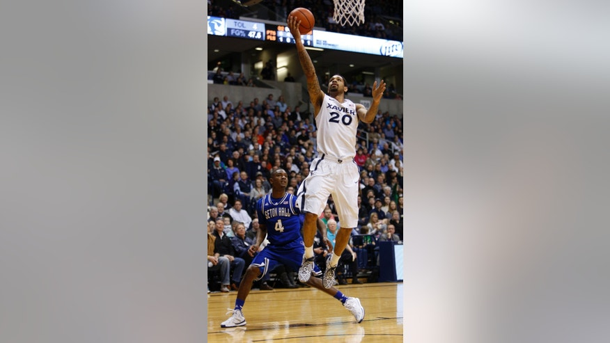 Xavier forward Justin Martin (20) goes up for a basket against Seton Hall guard Sterling Gibbs (4) during the first half of an NCAA college basketball game, Saturday, Feb. 1, 2014, in Cincinnati. (AP Photo/David Kohl)