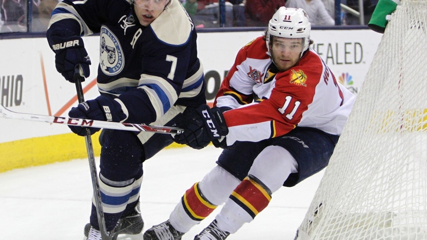 Columbus Blue Jackets' Jack Johnson, left, clears the puck as Florida Panthers' Jonathan Huberdeau defends during the first period of an NHL hockey game on Saturday, Feb. 1, 2014, in Columbus, Ohio. (AP Photo/Jay LaPrete)