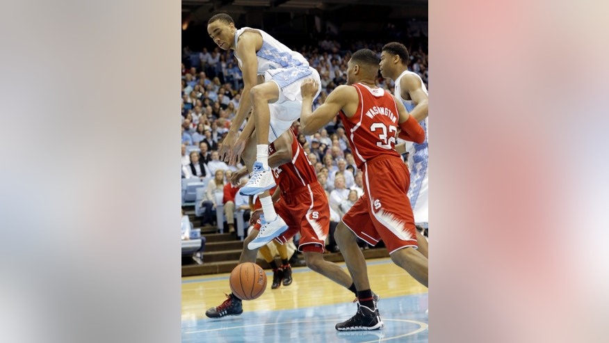 North Carolina's Brice Johnson jumps for a rebound against North Carolina State's Kyle Washington (32) and T.J. Warren, left, during the first half of an NCAA college basketball game in Chapel Hill, N.C., Saturday, Feb. 1, 2014. (AP Photo/Gerry Broome)