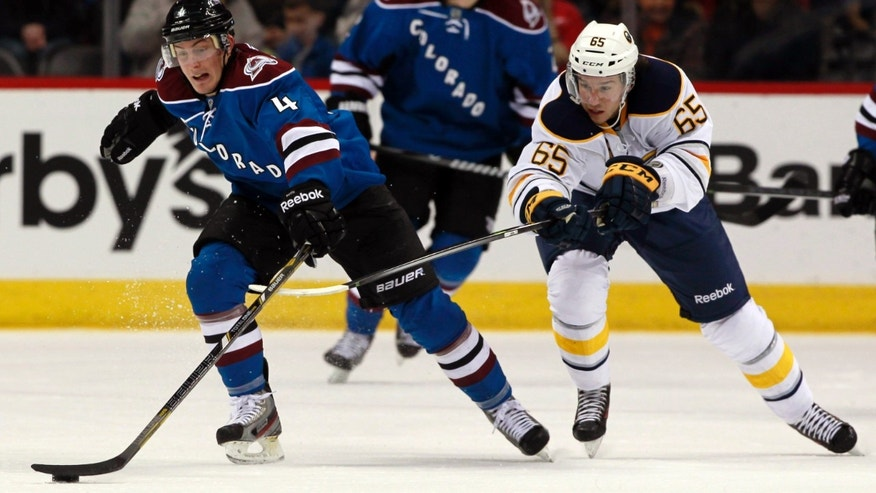 Colorado Avalanche defenseman Nick Holden, left, reaches out for puck as Buffalo Sabres center Brian Flynn covers in the second period of an NHL hockey game in Denver, Saturday, Feb. 1, 2014. (AP Photo/David Zalubowski)